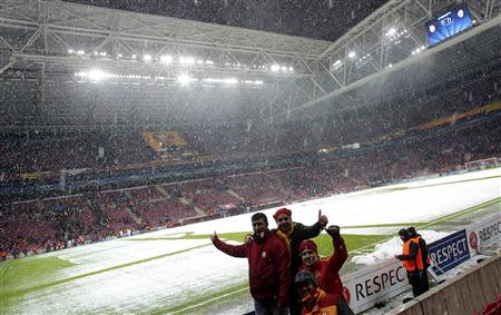 Supporters of Galatasaray cheer after the Champions League soccer match of their team against Juventus has been postponed due adverse weather conditions and the state of the pitch in Istanbul December 10, 2013. REUTERS/Murad Sezer