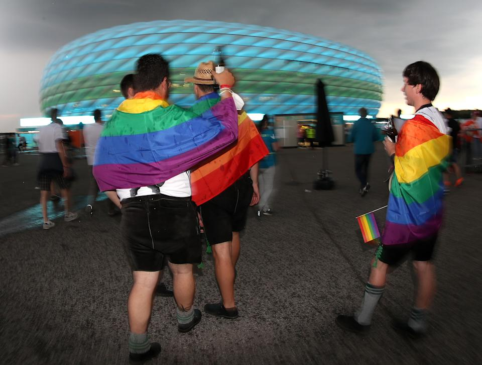 UNSPECIFIED, GERMANY - JUNE 23: Fans of Germany covered with rainbow flags toast with beer in front of the Allianz Arena soccer stadium illuminated in green and blue ahead of the Euro 2020 Group F match between Germany and Hungary on June 23, 2021 in Munich, Germany during EURO 2020.  (Photo by Alexandra Beier/Getty Images)