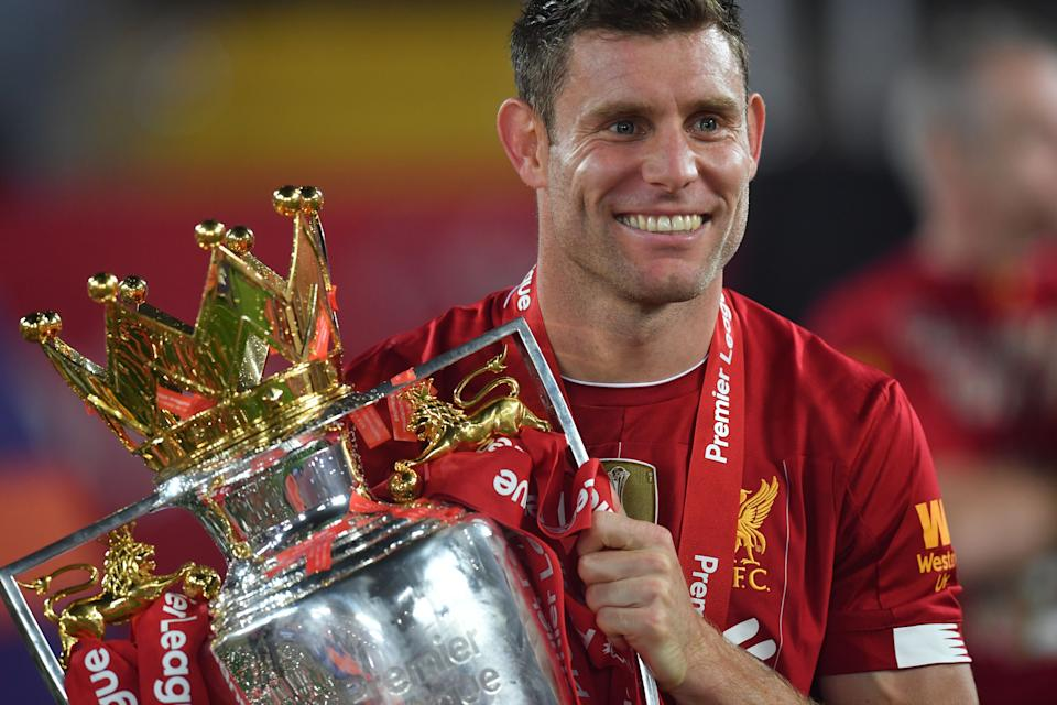 Liverpool's English midfielder James Milner poses with the Premier League trophy during the presentation following the English Premier League football match between Liverpool and Chelsea at Anfield in Liverpool, north west England on July 22, 2020. - Liverpool on Wednesday lifted the Premier League trophy at the famous Kop stand at Anfield after their final home game of the season. With no fans able to attend due to the COVID-19 coronavirus pandemic, Liverpool said the idea for the trophy lift was to honour the club's fans, but Liverpool manager Jurgen Klopp urged fans to respect social distancing measures, after thousands gathered around the club's stadium and in the city centre following their coronation as champions last month. (Photo by Paul ELLIS / POOL / AFP) / RESTRICTED TO EDITORIAL USE. No use with unauthorized audio, video, data, fixture lists, club/league logos or 'live' services. Online in-match use limited to 120 images. An additional 40 images may be used in extra time. No video emulation. Social media in-match use limited to 120 images. An additional 40 images may be used in extra time. No use in betting publications, games or single club/league/player publications. /  (Photo by PAUL ELLIS/POOL/AFP via Getty Images)