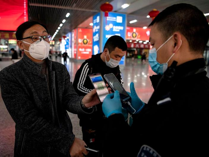 A passenger shows a green QR code on his phone at Wenzhou railway station on February 28, 2020.