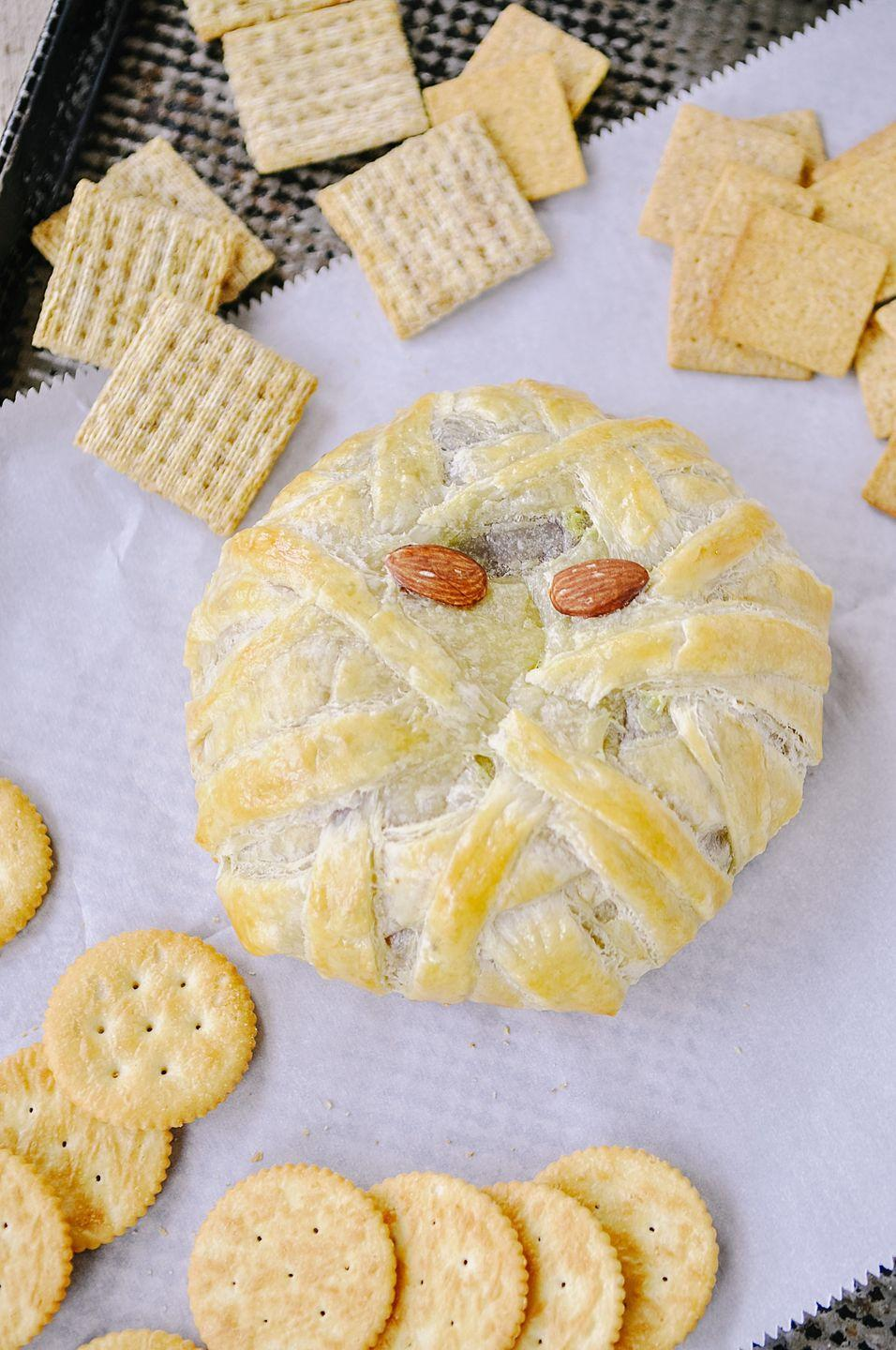 """<p>This adorable-as-can-be mummy isn't a bit scary because it only takes a few minutes to whip it up with puff pastry. </p><p><a class=""""link rapid-noclick-resp"""" href=""""https://www.yourhomebasedmom.com/mummy-wrapped-brie-and-halloween-dinner-party/"""" rel=""""nofollow noopener"""" target=""""_blank"""" data-ylk=""""slk:GET THE RECIPE"""">GET THE RECIPE</a></p>"""