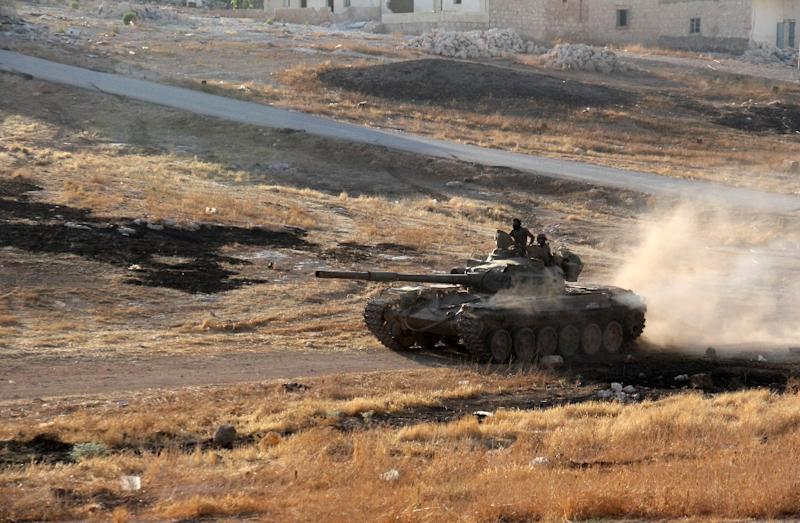 Opposition fighters drive a tank in the Al-Huweiz area on southern outskirts of Aleppo as they battle to break the government seige on the northen Syrian city on August 2, 2016 (AFP Photo/Omar haj kadour)