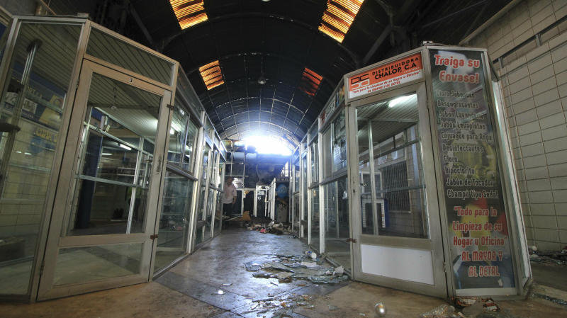 The hallway of a mall is trashed after stores stand empty one day after it was looted in Maracaibo, Venezuela, Wednesday, March 13, 2019. Venezuela's largest private food supplier says massive looting and vandalism occurred at four facilities in the city of Maracaibo during nationwide power outages, complicating efforts to distribute food and drinks to people in the area. (AP Photo/Henry Chirinos)