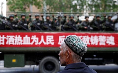 A Uighur man looks on as a truck carrying paramilitary policemen travel along a street during an anti-terrorism oath-taking rally in Urumqi, Xinjiang in 2014 - Credit: REUTERS
