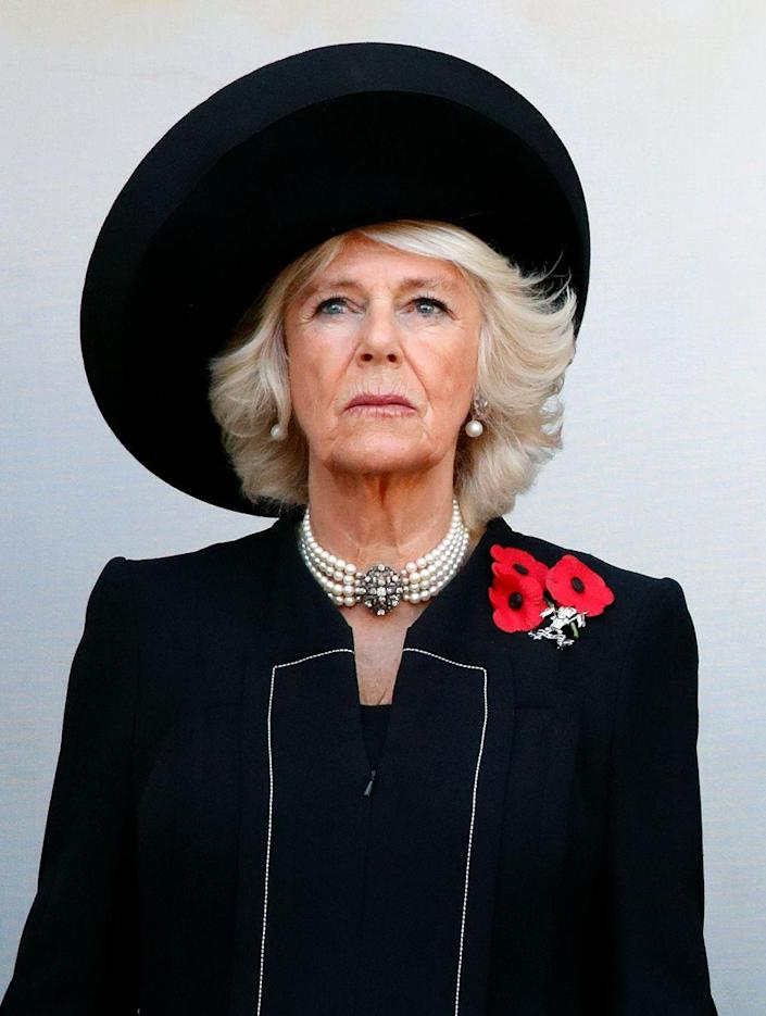 """<p>Camilla the Duchess of Cornwall observes <a href=""""https://www.townandcountrymag.com/society/tradition/g24854110/royal-family-remembrance-day-service-2018-photos/"""" rel=""""nofollow noopener"""" target=""""_blank"""" data-ylk=""""slk:the annual Remembrance Sunday Service"""" class=""""link rapid-noclick-resp"""">the annual Remembrance Sunday Service</a> at the Cenotaph, where the royal family paid respect to the servicemen on the 100th anniversary of World War I. For the somber occasion, Camilla wore a wide brimmed black hat, a pearl choker and earrings, and a black coat with three poppy pins. </p>"""