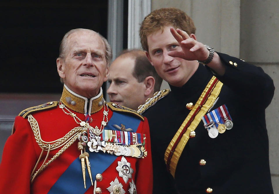 """FILE - In this June 14, 2014 file photo, Britain's Prince Harry talks to Prince Philip, left, as members of the Royal family appear on the balcony of Buckingham Palace, during the Trooping The Colour parade, in central London. In the TV program 'Prince Philip: The Royal Family Remembers' released late Saturday Sept. 18, 2021, members of the royal family spoke admiringly of the late Duke of Edinburgh's barbecuing skills and Prince Harry described how his grandfather would """"never probe"""" but listen intently about his two tour of duties to Helmand province during the war in Afghanistan. (AP Photo/Lefteris Pitarakis, File)"""