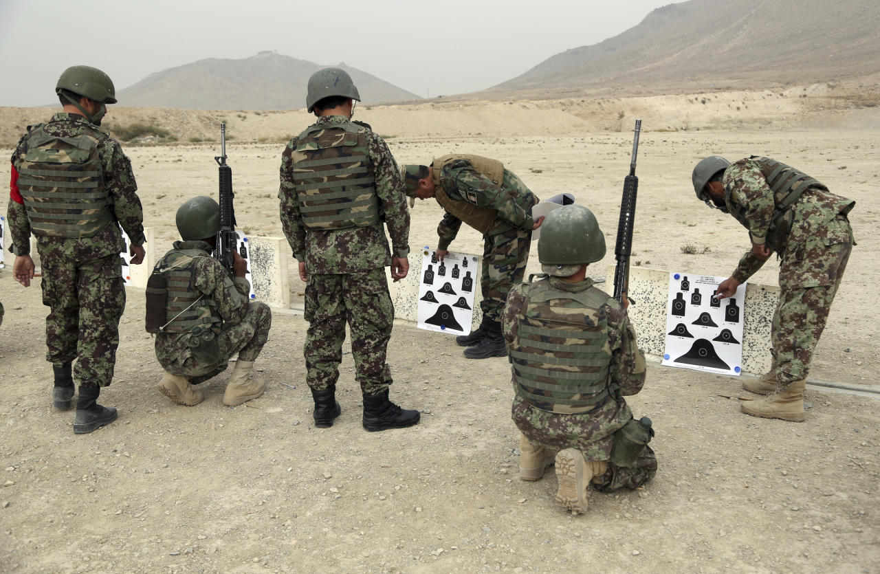 In this Oct. 31, 2018 photo, Afghan National Army teachers inspect the accuracy during a live fire exercise, at the Afghan Military Academy in Kabul, Afghanistan. When U.S. forces and their Afghan allies rode into Kabul in November 2001 they were greeted as liberators. But after 17 years of war, the Taliban have retaken half the country, security is worse than it's ever been, and many Afghans place the blame squarely on the Americans. (AP Photo/Rahmat Gul)