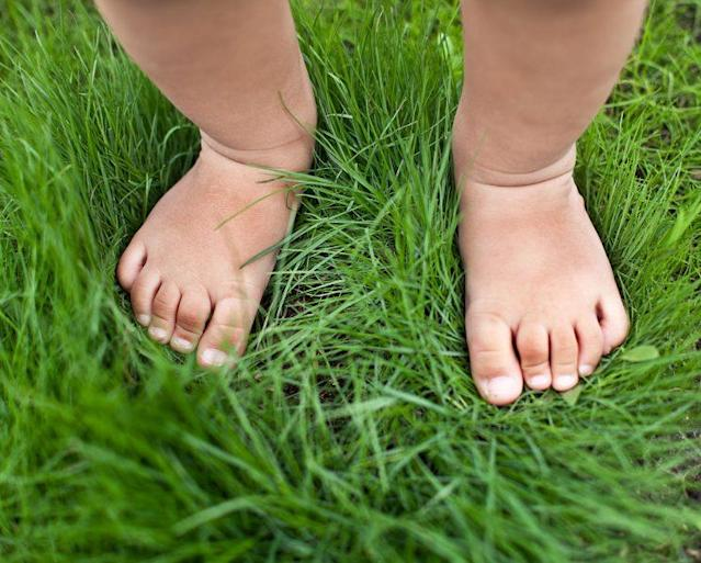 Barefoot walks in the grass may not be so harmless, due to ticks. (Photo: Getty Images)