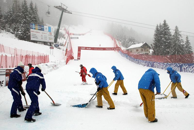 Course workers clear the snow in the finish area ahead of a men's Alpine Ski World Cup downhill race ,in Val Gardena, Italy, Saturday, Dec. 15, 2012. (AP Photo/Armando Trovati)