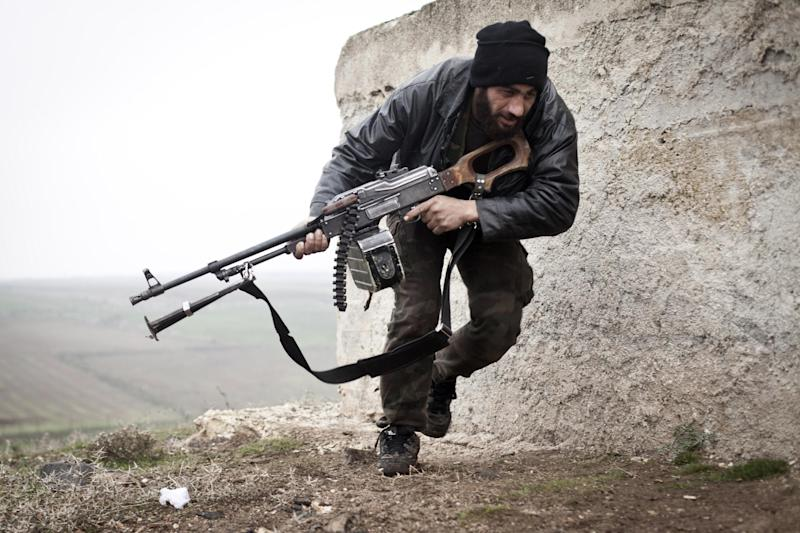 FILE - In this December 17, 2012, file photo, a Free Syrian Army fighter takes cover during fighting with the Syrian Army in Azaz, Syria. Al-Qaida-linked gunmen in northern Syria captured a town near the Turkish border Thursday, Sept. 19, 2013, following heavy clashes with mainstream, Western-backed rebels in the area, prompting Turkey to close a nearby crossing, activists and Turkish officials said. (AP Photo/Virginie Nguyen Huang, File)