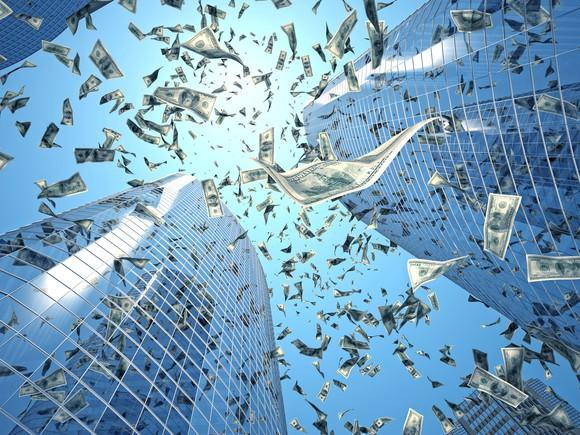 Paper currency falling from the sky in between skyscrapers.