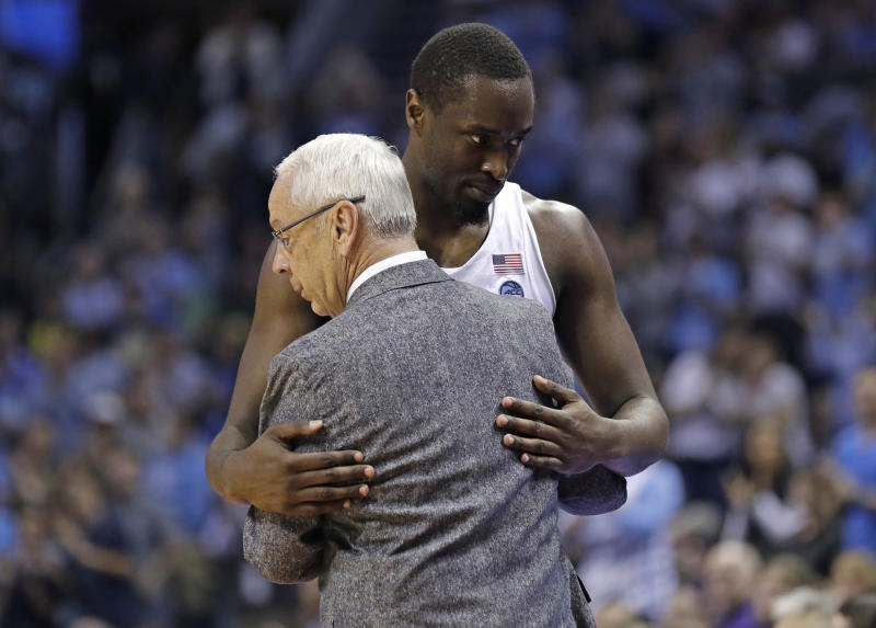 North Carolina head coach Roy Williams, front, hugs Theo Pinson, back, during the second half of a second-round game against Texas A&M in the NCAA men's college basketball tournament in Charlotte, N.C., Sunday, March 18, 2018. (AP Photo/Gerry Broome)