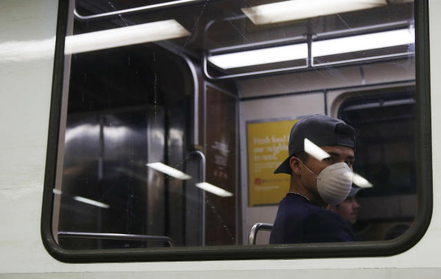 A commuter wears a protective face mask as he rides the train in Boston amid stay-at-home orders that apply to all but essential workers. (Photo by Jessica Rinaldi/The Boston Globe via Getty Images)