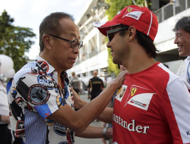 Property tycoon Ong Beng Seng (L), credited as one of the key people responsible for bringing the Formula One to Singapore, greets Ferrari Formula One driver Felipe Massa of Brazil during the Singapore F1 Grand Prix at the Marina Bay street circuit in Singapore September 22, 2013. REUTERS/Tim Chong (SINGAPORE - Tags: SPORT MOTORSPORT F1 BUSINESS)