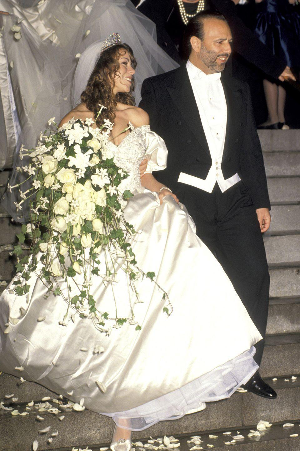 <p>It's no surprise that the diva went all out for her first wedding to Tommy Mottola, including having 50 flower girls. Designed by Vera Wang, her gown had puffy, off-the-shoulder sleeves and a 27-foot train, completed with a tiara and 10-foot veil.</p>