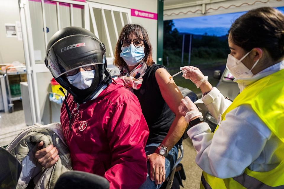 ROME, ITALY - MAY 15: A nurse inoculating a woman on a motorbike with the Astrazeneca vaccine at the Valmontone vaccination centre on May 15, 2021 in Rome, Italy. Astrazeneca vaccination open day for the over 40s until midnight at Italy's largest drive-through. The vaccination centre in the Valmontone Outlet car park (Rome) covers an area of 20,000 square metres. (Photo by Fabrizio Villa/Getty Images) (Photo: Fabrizio Villa via Getty Images)