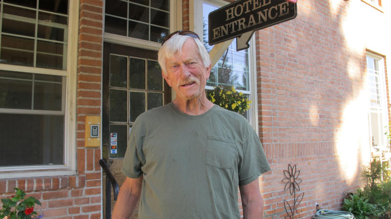 In this Wednesday, July 31, 2019 photo Arlie Ward, owner of a hotel, discusses the impact of the closure of the nearby Pend Oreille Mine in downtown Metaline Falls, Wash. The mine closure will cost 200 good-paying jobs in the rural area. (AP Photo/Nicholas K. Geranios)