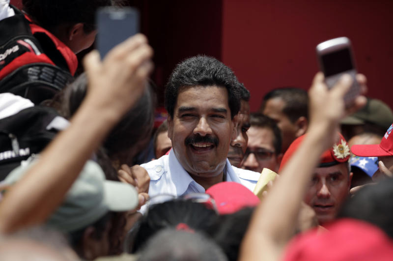 Venezuela's interim President Nicolas Maduro smiles as he's surrounded by supporters during a campaign rally in Sabaneta, Barinas state, Venezuela, Tuesday, April 2, 2013. Late President Hugo Chavez's chosen successor, Nicolas Maduro is competing against opposition leader Henrique Capriles in the April 14 presidential election. (AP Photo/Ariana Cubillos)