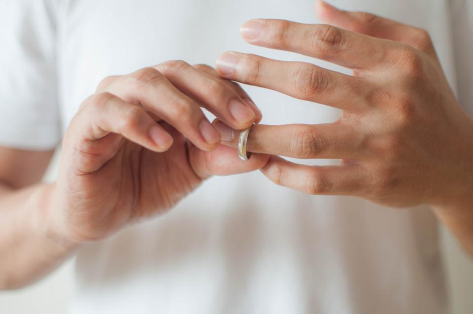 man's hands removing his wedding ring cheating