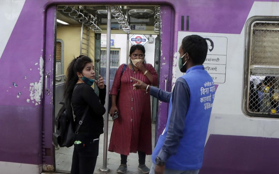 A municipal worker gives a commuter a penalty for not using a face mask at Chhatrapati Shivaji Maharaj Terminus in Mumbai, India, Saturday, Feb. 20, 2021. Health officials have detected a spike in COVID-19 cases in several pockets of Maharashtra state, including in Mumbai, the country's financial capital. (AP Photo/Rajanish Kakade)