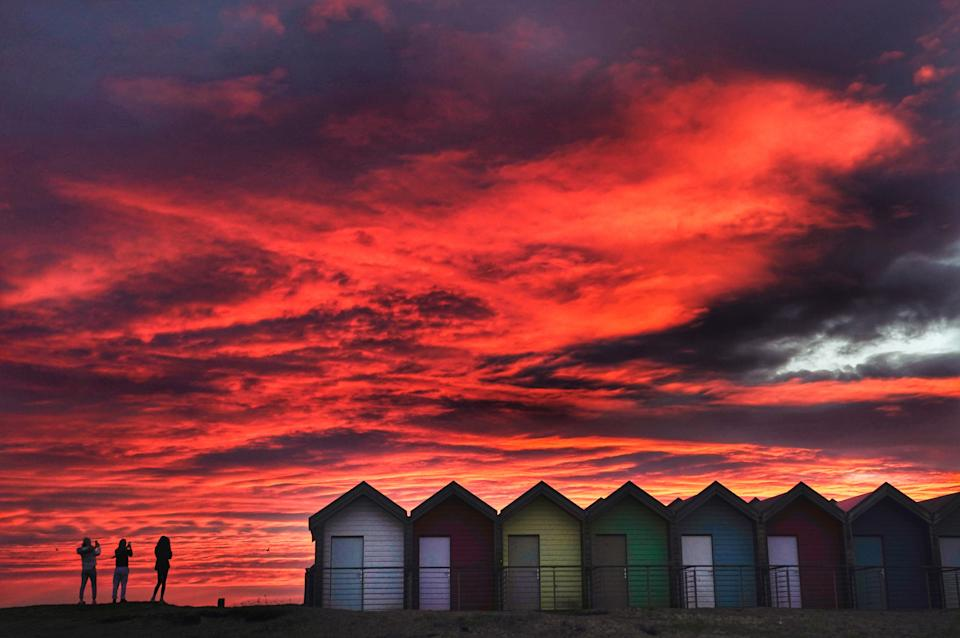 Colourful beach huts stand in front of the stunning red sky at sunrise in Blyth, Northumberland. Picture date: Tuesday February 23, 2021. (Photo by Owen Humphreys/PA Images via Getty Images)