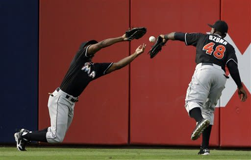 Miami Marlins' Juan Pierre, left, and Marcell Ozuna, fail to catch a sacrifice fly by Atlanta Braves' Freddie Freeman allowing teammate Justin Upton to score in the fourth inning of a baseball game, Tuesday, July 2, 2013, in Atlanta. A fielding error was given to Juan Pierre on the play. (AP Photo/David Goldman)