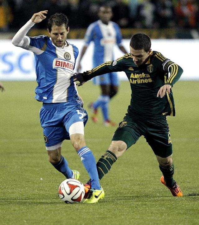 Philadelphia Union midfielder Vincent Nogueira, left, and Portland Timbers midfielder Will Johnson fight for the ball during the first half of an MLS soccer game in Portland, Ore., Saturday, March 8, 2014. (AP Photo/Don Ryan)