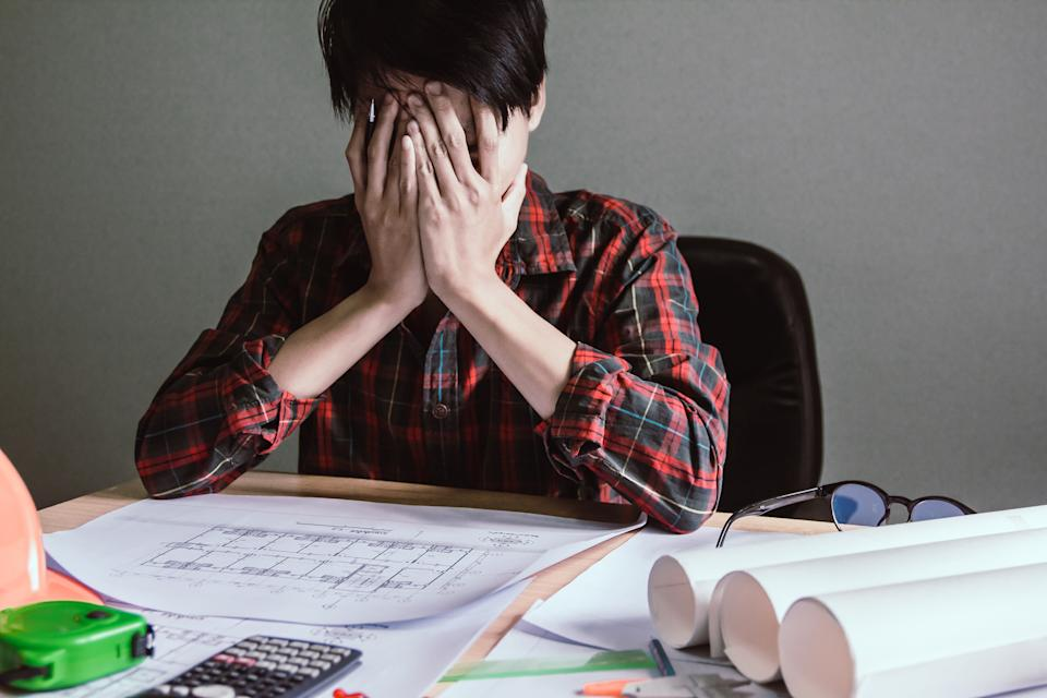 Asian young man are stress worry probleme working sitting on chair in office.
