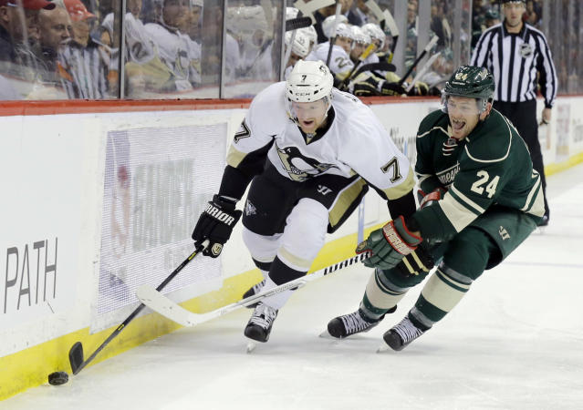 Pittsburgh Penguins defenseman Paul Martin (7) controls the puck in front of Minnesota Wild left wing Matt Cooke (24) during the second period of an NHL hockey game in St. Paul, Minn., Saturday, April 5, 2014. (AP Photo/Ann Heisenfelt)