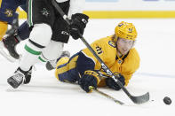 Nashville Predators center Rem Pitlick (16) reaches for the puck as he falls in the second period of an NHL hockey game between the Predators and the Dallas Stars Sunday, April 11, 2021, in Nashville, Tenn. (AP Photo/Mark Humphrey)