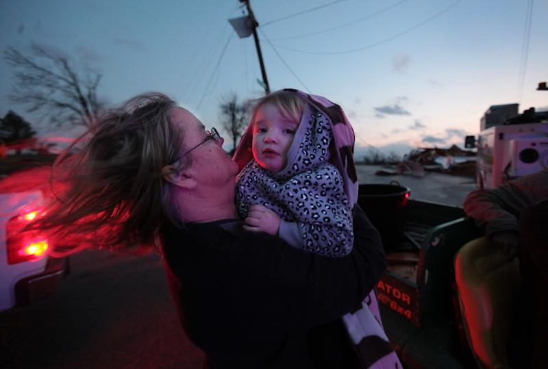 Sandy Ryan, holds her granddaughter, Maci Becraft, in Metro Piner, Ky., after a tornado swept through the area Friday, March, 2, 2012. The front of Becraft's house was destroyed due to the tornado and Ryan is attempting to locate other Becraft family members. Powerful storms stretching from the U.S. Gulf Coast to the Great Lakes in the north wrecked two small towns, killed over a dozen, and bred anxiety across a wide swath of the country on Friday, in the second deadly tornado outbreak this week. (AP Photo/The Cincinnati Enquirer, Carrie Cochran) MANDATORY CREDIT; NO SALES