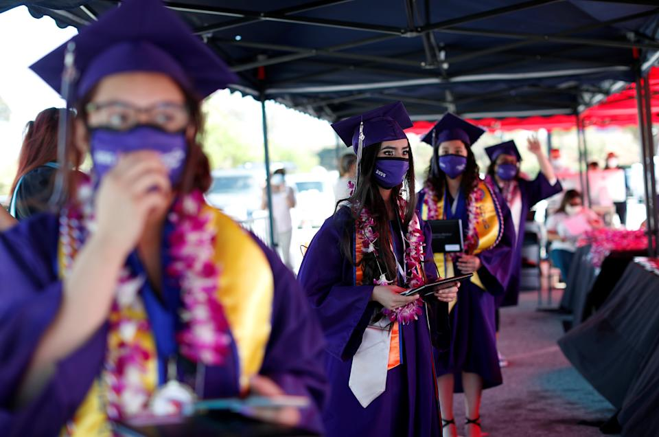 Compton Early College High School graduating students wait after picking up their diplomas in a parking lot during a drive-thru graduating ceremony, during the outbreak of the coronavirus disease (COVID-19) in Compton, California U.S. June 10, 2020. REUTERS/Mario Anzuoni