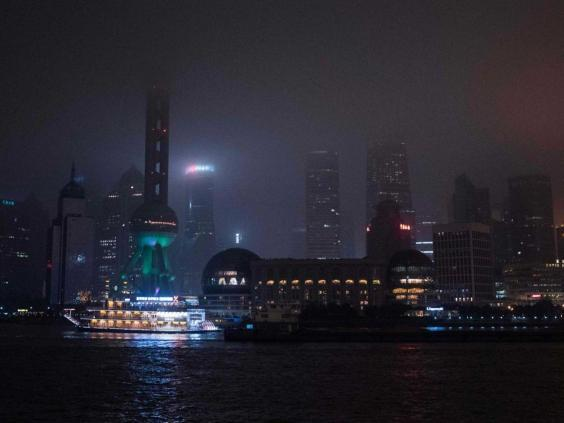A well-lit ferry stands out from a darkened Shanghai skyline during Earth Hour 2016 (AFP/Getty)