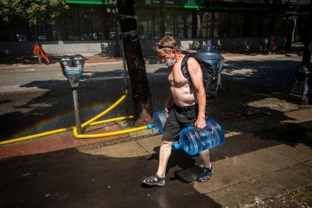 A man carrying multiple jugs of water walks through a sprinkler during a period of record breaking temperatures in Vancouver on Monday. (Ben Nelms/CBC - image credit)