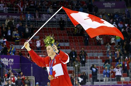 Canada's Jonathan Toews carries his country's flag after his team defeated Sweden in the men's ice hockey final game at the 2014 Sochi Winter Olympic Games, February 23, 2014. REUTERS/Brian Snyder