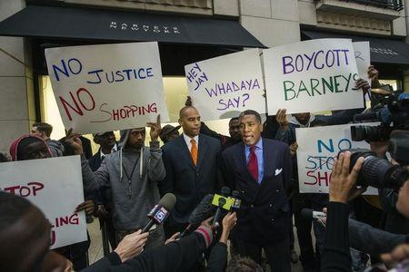 Reverend Conrad Tillard speaks in front of a Barneys luxury department store while standing with demonstrators holding signs decrying allegations that Barney's and Macy's stores have unfair security policies aimed at minorities in New York