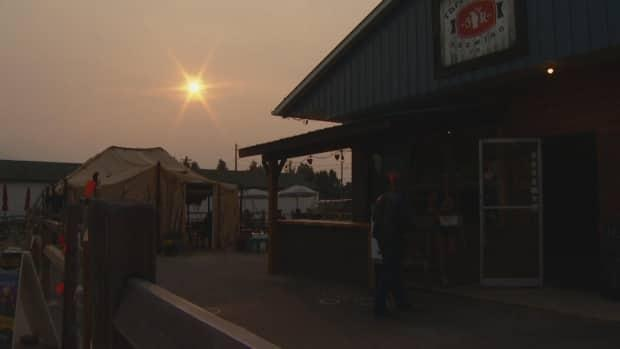 People enter the local brewery under smoky skies in Valemount, B.C., in early July 2021.  (Michael McArthur/CBC - image credit)