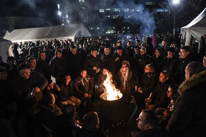 Opposition party supporters keep warm by a fire as they gather in front of Kosovo's government building in Pristina on February 24, 2016, to demand the resignation of the government (AFP Photo/Armend Nimani)