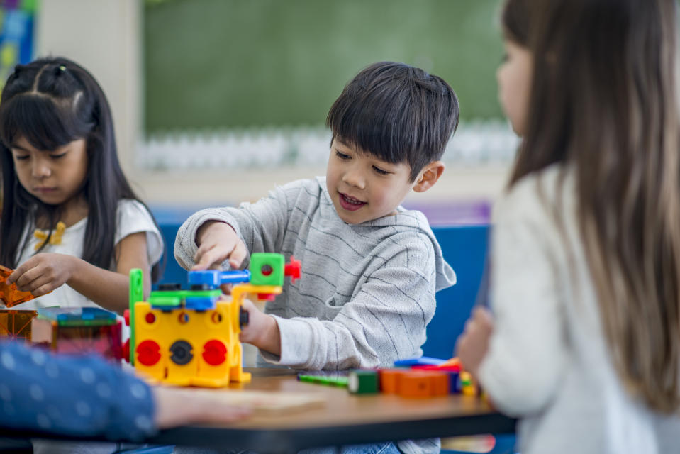 A group of preschool students are indoors in their classroom. They  are sitting with their teacher and playing with building blocks.