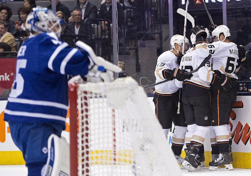 Toronto Maple Leafs goalie Jonathan Bernier, left, looks on as the Anaheim Ducks celebrate a goal by Nick Bonino (13) during the first period of an NHL hockey game in Toronto on Tuesday, Oct. 22, 2013. (AP Photo/The Canadian Press, Nathan Denette)
