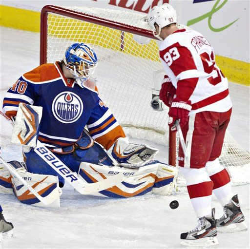 Detroit Red Wings' Johan Franzen (93) is stopped by Edmonton Oilers goalie Devan Dubnyk (40) during the first period of an NHL hockey game Friday, March 15, 2013, in Edmonton, Alberta. (AP Photo/The Canadian Press, Jason Franson)