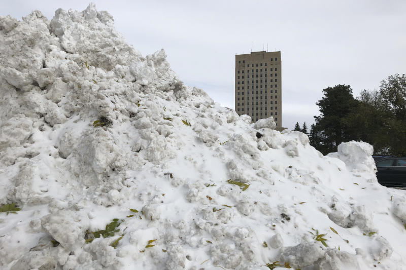 Snow is piled high in front of the state Capitol in Bismarck, N.D. on Friday Oct. 11, 2019. North Dakota Gov. Doug Burgum activated the state's emergency plan due to what he called a crippling snowstorm that closed major highways and had farmers and ranchers bracing for huge crop and livestock losses. (AP Photo/James MacPherson)