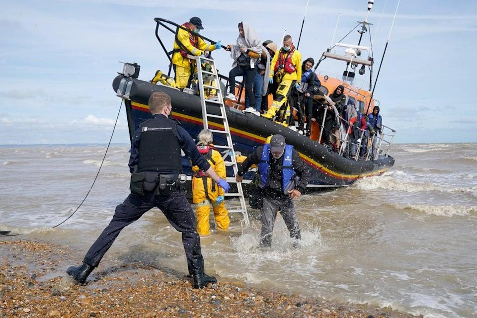 Immigration Enforcement officers and members of the RNLI assist a group of people thought to be migrants from an RNLI lifeboat after they were brought into Dungeness, Kent (Gareth Fuller/PA) (PA Wire)