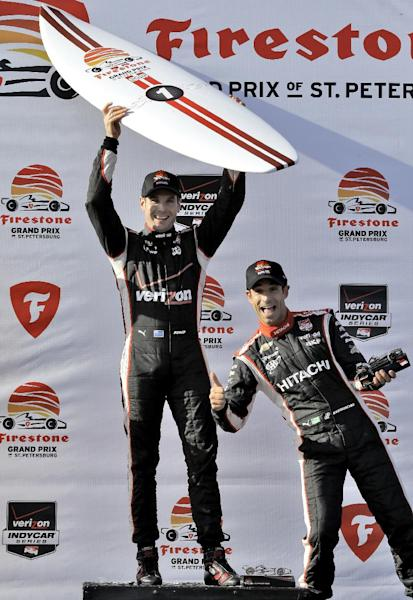Third-place finisher Helio Castroneves, right, of Brazil, jumps in the photo as Will Power, of Australia, poses with his surfboard after Power won the IndyCar Grand Prix of St. Petersburg auto race, Sunday, March 30, 2014, in St. Petersburg, Fla. (AP Photo/Chris O'Meara)