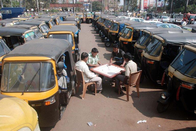 Striking Indian auto-rickshaw drivers play carrom amid their vehicles at an auto stand during a two-day strike called by trade unions opposing the government's economic policies in Bhubaneswar on February 20, 2013. Financial services and transport were hit by the strike called by 11 major workers' groups to protest against pro-market economic reforms announced by the government last year