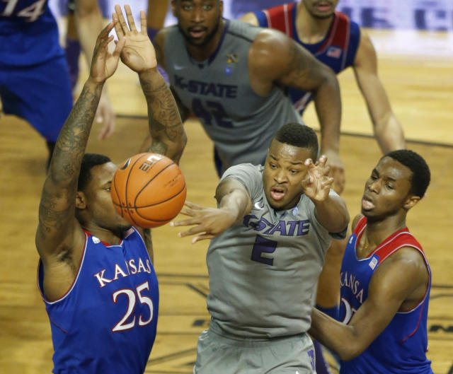 Kansas State guard Marcus Foster (2) passes to a teammate while covered by Kansas guard Andrew Wiggins, right, and forward Tarik Black (25) during the second half of an NCAA college basketball game in Manhattan, Kan., Monday, Feb. 10, 2014. Kansas State defeated Kansas 85-82 in overtime. (AP Photo/Orlin Wagner)
