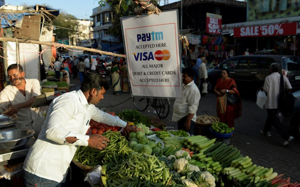 A sign advertising Indian electronic and cellpohne-based payment system PAYTM hangs at a roadside vegetable stall in Mumbai on February 25, 2017.  / AFP / PUNIT PARANJPE        (Photo credit should read PUNIT PARANJPE/AFP/Getty Images)