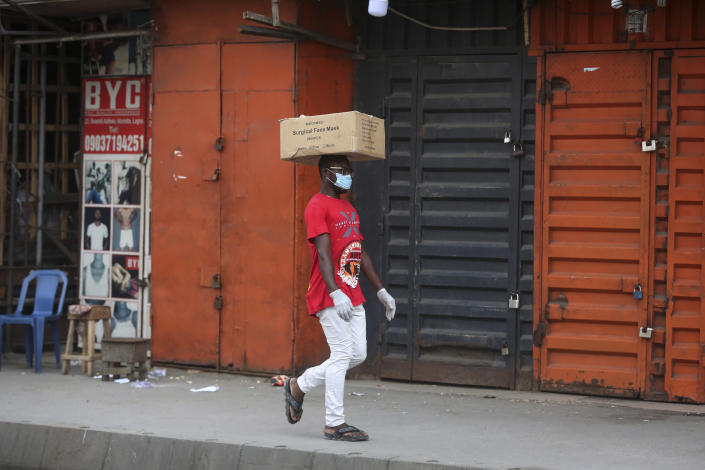 A man carries a box of surgical face masks on his head while wearing one, as he walks past closed shops due to a government ban on the operation of non-essential businesses and markets to halt the spread of the new coronavirus, in Lagos, Nigeria Thursday, March 26, 2020. The new coronavirus causes mild or moderate symptoms for most people, but for some, especially older adults and people with existing health problems, it can cause more severe illness or death. (AP Photo/Sunday Alamba)