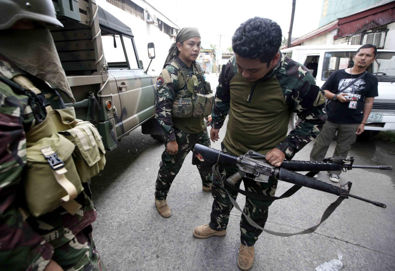 Government troopers look at two M-16 automatic rifles recovered from Muslim rebels who were killed in the offensive, Sunday Sept. 15, 2013 in Zamboanga city, southern Philippines The standoff, which began Monday when about 200 Moro National Liberation Front guerrillas stormed several coastal communities in Zamboanga city and seized several residents, has displaced more than 60,000, forced the closure of businesses and resulted in more than 50 deaths so far. (AP Photo/Bullit Marquez)