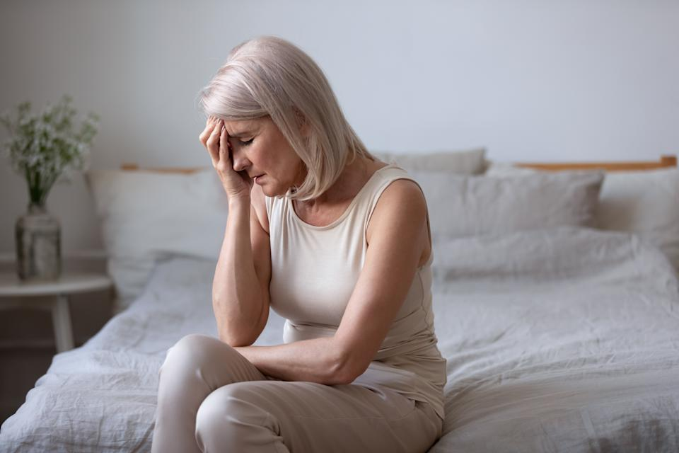 Seated in bed in the morning middle-aged woman touch face with hand closed eyes suffers from barometric pressure headache migraine, old female feels unhappy upset health or personal problems concept